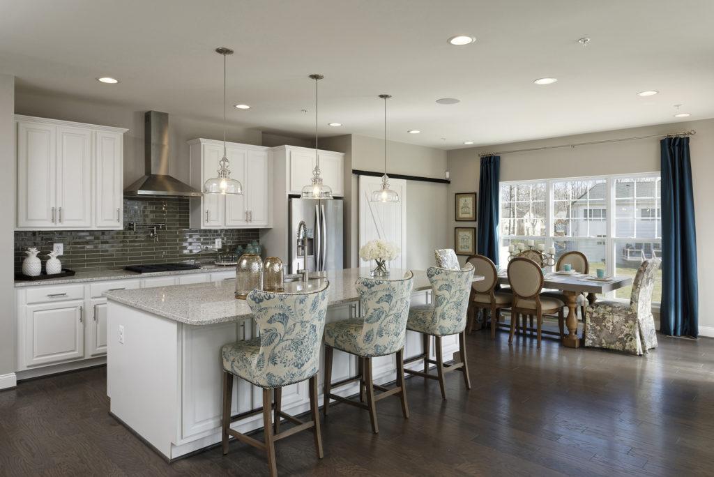 Popular white kitchen with quartz counters, barn door, Progress pendant lights